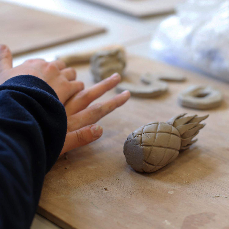 Mains pétrissant de la terre dans un atelier céramique