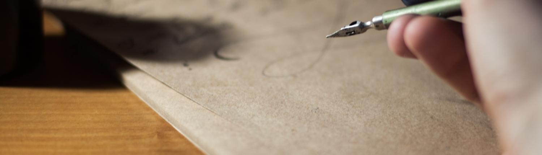 Personne écrivant à la plume sur du vieux papier