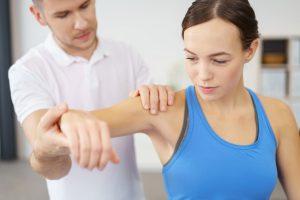 Un osteopathe manipule le bras d'une patiente