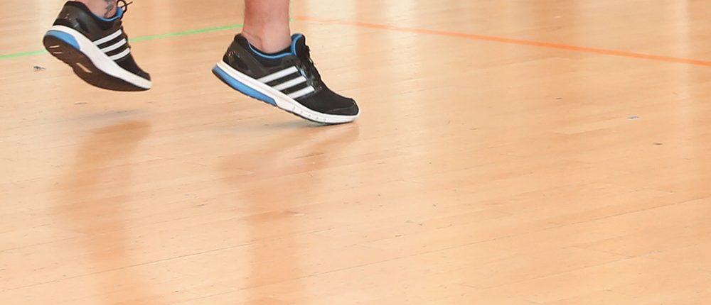 Un homme en baskets saute dans une salle de sport